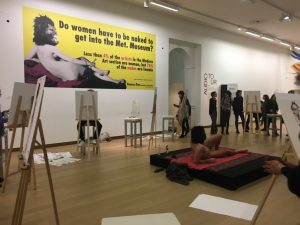 The live model drawing session. The male model posing as the nude in the Guerrilla Girls poster from 2012, shown in the background