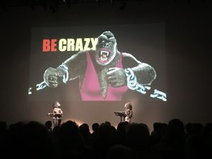 "Presentation of the Guerilla Girls: Picture of a female gorilla in a pink bathing suit, with the wrods ""Be crazy"" written on the picture"
